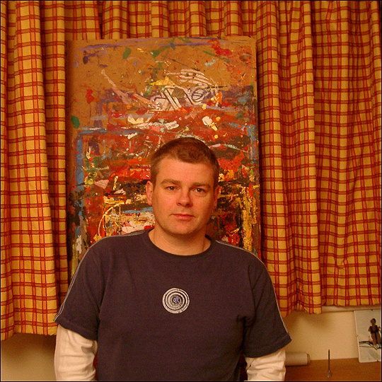 Mark Haddon stands in front of an abstract painting.