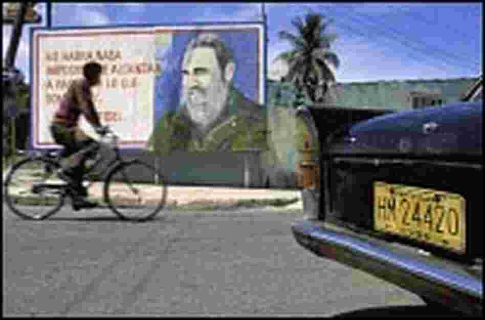 A bicyclist in 1994 rides past a billboard in Havana.