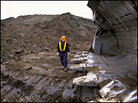 Man Standing in Oil Pit with Giant Shovel