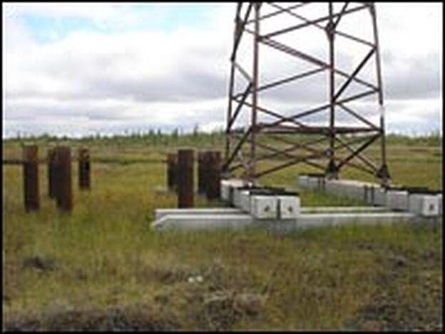 Pylons holding electric wires are being moved from tilting piles driven into the melting permafrost 30 years ago onto more stable horizontal concrete ties.