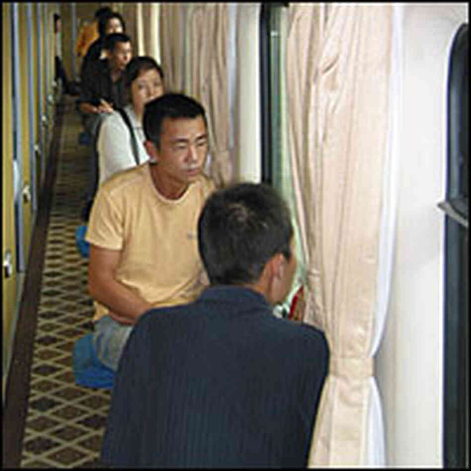 Passengers on the Beijing to Lhasa train sit outside their sleeping compartments.
