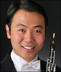Liang Wang, pictured in tuxedo, holding his oboe. - wang200x235-d4328596641e2d18216a5b6e03940edea2381fc9-s300-c85