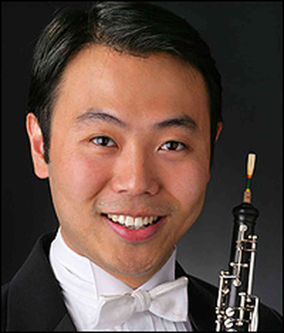 Liang Wang, pictured in tuxedo, holding his oboe.
