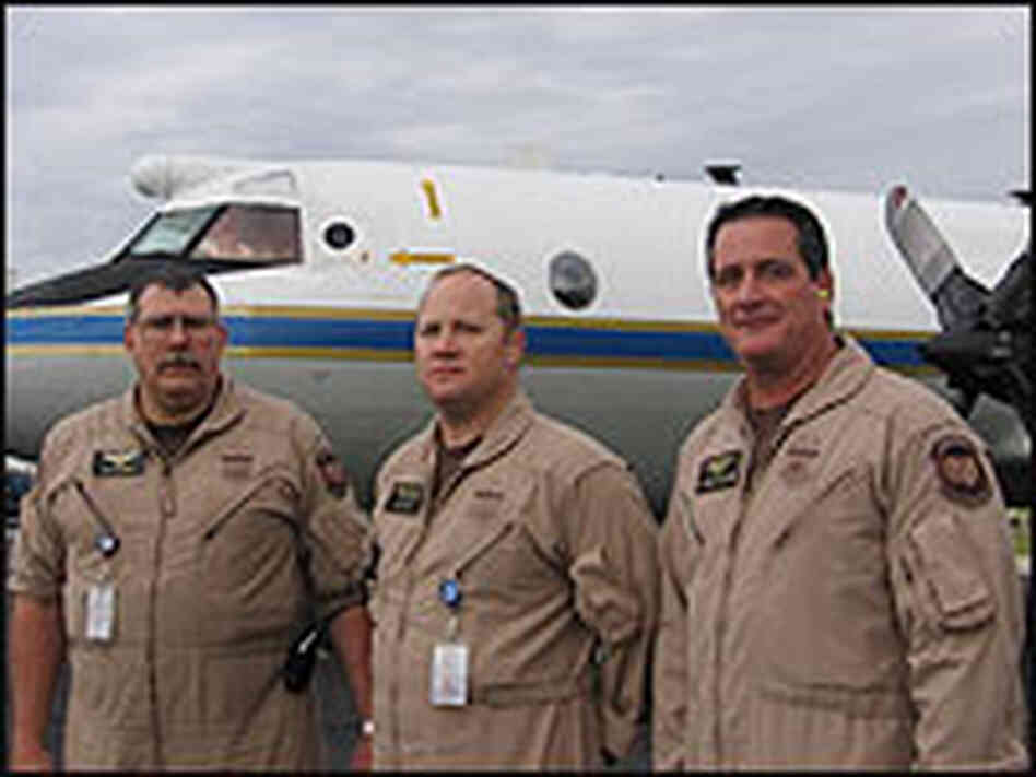 Detection systems specialists standing in front of and aircraft used to seize illegal drugs.