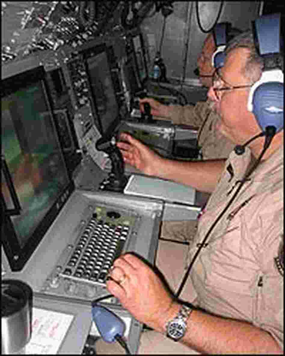 Senior Detection Systems Speicalist Dan Williams sitting at a console in a plane, using radar.