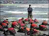Navy SEAL recruits participate in a surf drill on the beach, guided by an instructor.