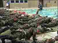 Navy SEAL recruits do push-ups by a pool while an instructor explains swim techniques.