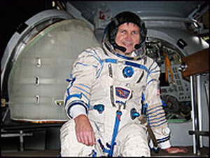 Charles Simonyi, in astronaut gear, in front of the Soyuz simulator.