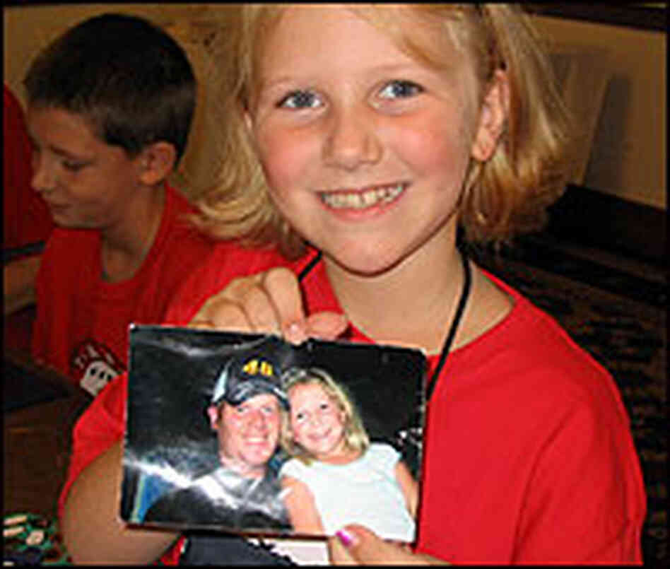 Katie Staats, 8, shows a picture taken with her father.