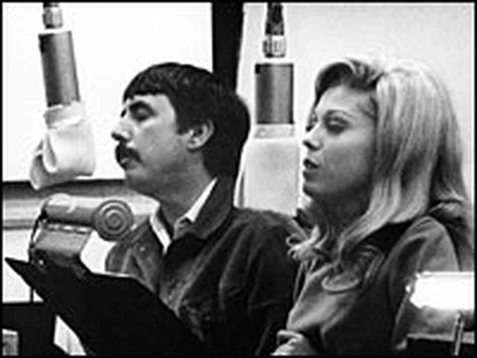 Lee Hazlewood and Nancy Sinatra, seated at music stands and microphones, sing in a recording studio