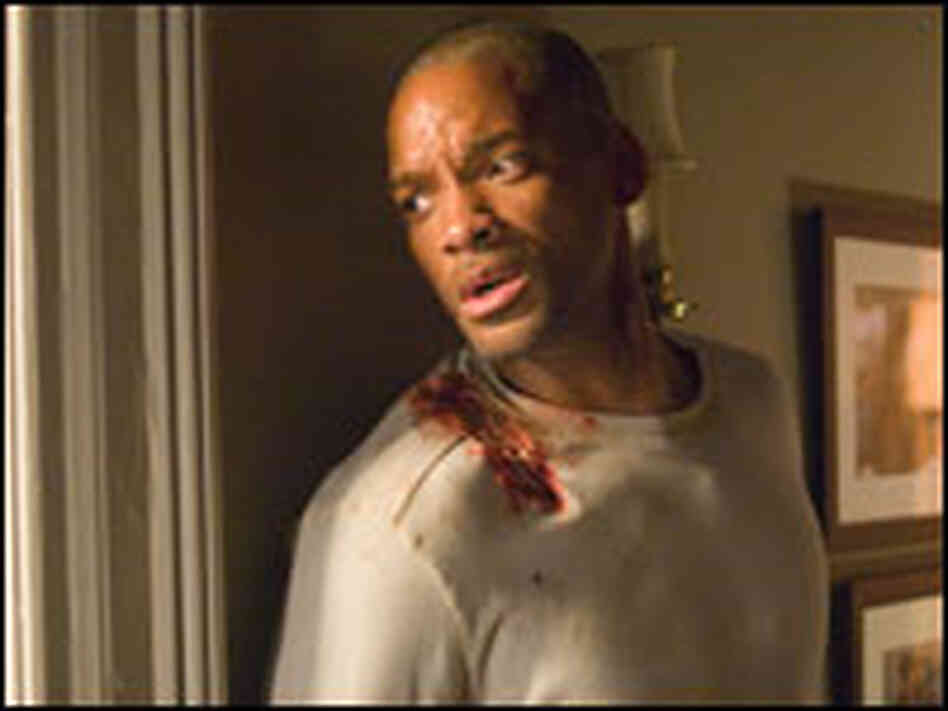 "Actor Will Smith, with bloodied shoulder, looks nervously out window in ""I Am Legend."""