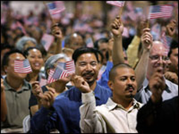 Immigrants wave flags after being sworn in as U.S. citizens in naturalization ceremonies last week in Pomona, Calif. Some of the 6,000 people taking their citizenship oath are part of a flood of immigrants trying to beat a Monday deadline when fees go up.