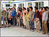 A group of slave laborers await identity check at a village police station after being rescued