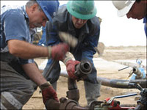 Oil Wokers Struggle to Repair Pump on Oil Well