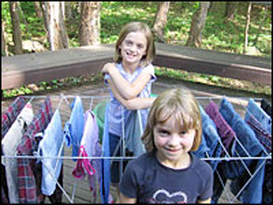 Daughters Nadia (back) and Anja stand with a rack of drying clothes on the family's deck.