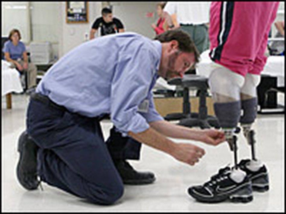 Prosthetist David Beachler adjusts Downes' prosthetic legs.