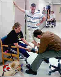 Sue Downes' husband, Gabe, looks on as prosthetist David Beachler adjusts her prosthetic leg.