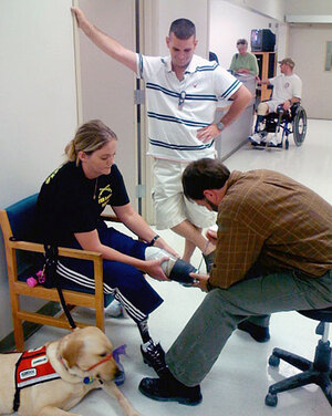 Sue Downes' husband, Gabe, looks on as prosthetist Beachler makes adjustments during an earlier session.