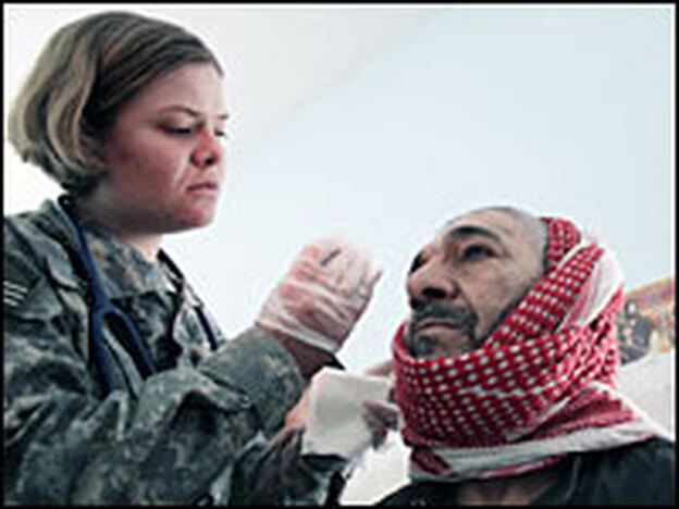 A medic with the U.S. Army's 82nd Airborne Division treats the wound of an Iraqi man in a temporary clinic in Baghdad's Sadr City in March 2007.