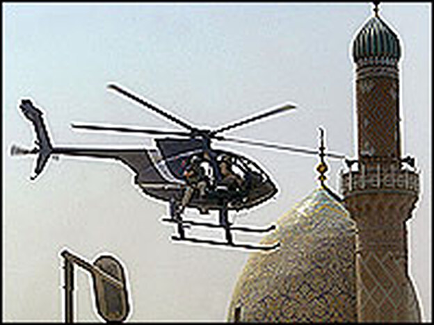 A Blackwater security firm helicopter flies low above a central Baghdad street.