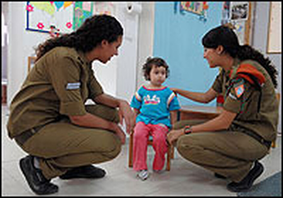 After a Qassam rocket attack by Palestinian militants from the Gaza strip, Israeli soldiers talk to a little girl at a nursery.