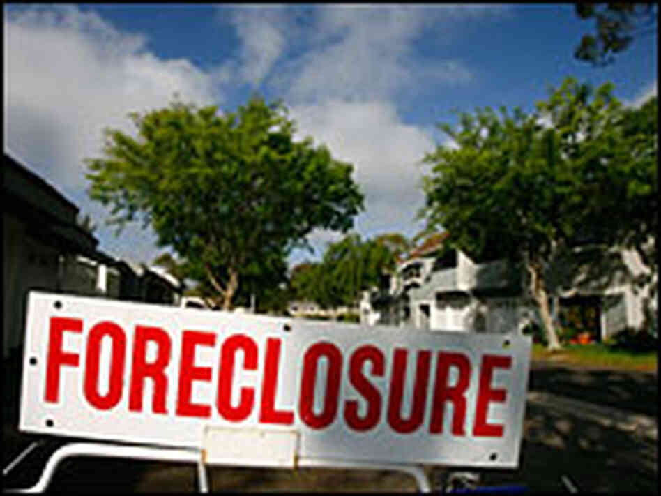 A foreclosure sign stands in the yard of a house.
