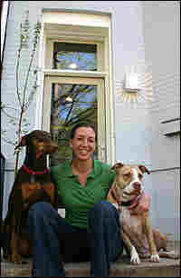 Amy Levin sits on the porch of her newly rehabbed environmentally-friend town house