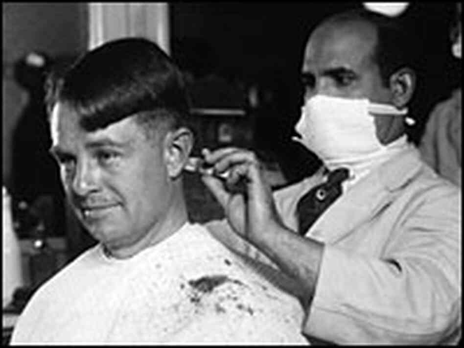A barber wears a face mask as protection from the flu virus in 1918.