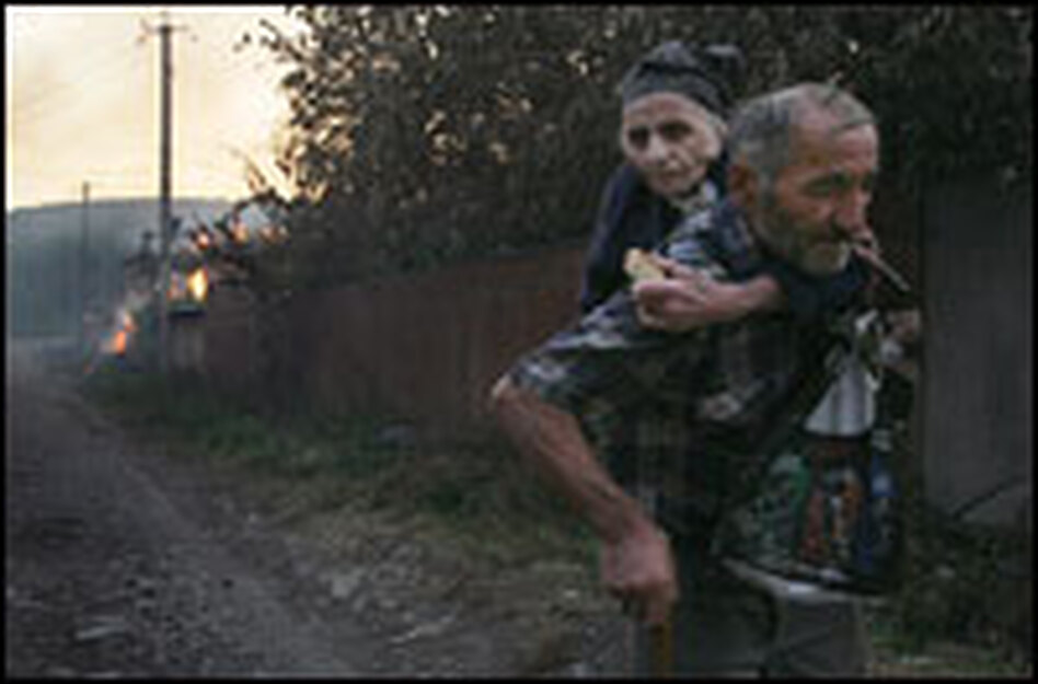 Georgians escape from a house set on fire in the village of Kvemo-Achebeti, outside the South Ossetian capital Tskhinvali, on Monday.