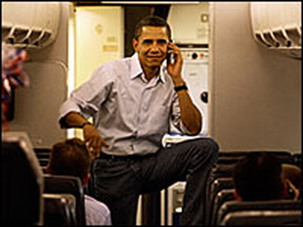 Democratic Sen. Barack Obama of Illinois talks on his cell phone as he boards his campaign plane in May.