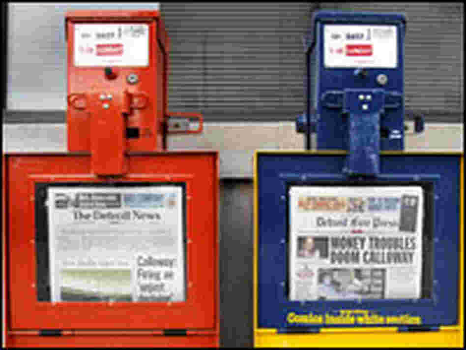 Detroit Free Press and Detroit News newspaper boxes stand in front of newspapers' building.