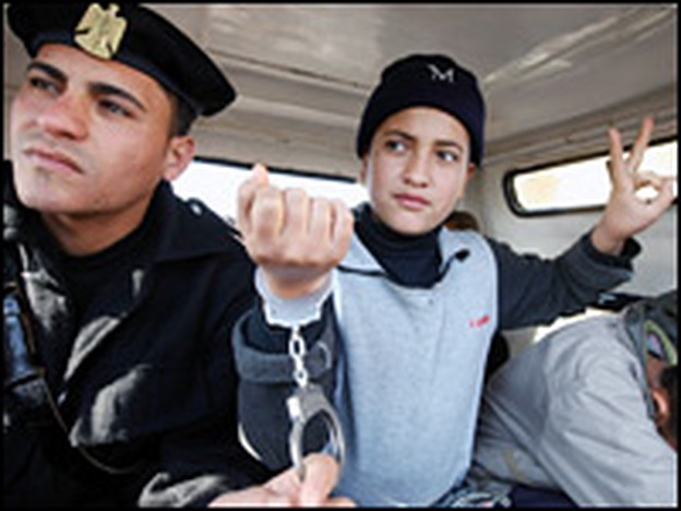 An Egyptian policeman sits with arrested Palestinian boys as they are returned to Gaza on Monday. The boys were caught after entering Egypt illegally over the Rafah border crossing between Egypt and the Gaza Strip.