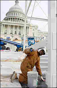 A worker paints the reviewing stand at the U.S. Capitol.