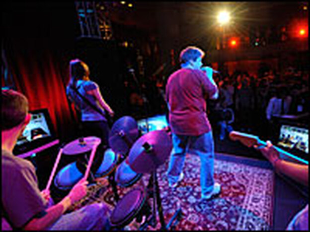 Guests at the July 2008 MTV Rock Band Party play <em>Rock Band 2</em> in the Orpheum Theatre in Los Angeles.  Some smaller venues, like bars, have purchased the game to attract more customers.