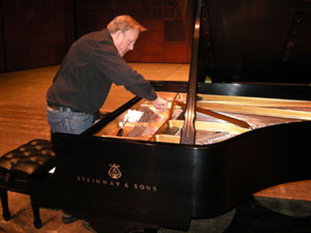 Eric Wolfley, director of piano services at CCM, tunes the Steinway Concert Grand Model D.