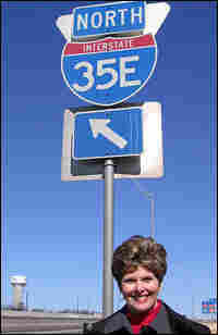 Cindy Jacobs stands in front of a blue highway sign that reads North Interstate 35E