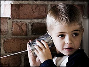 A boy listens with his tin-can phone.