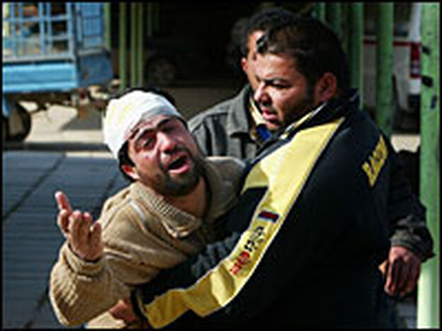 An injured Iraqi cries for his brother, who was killed in a bombing at a pet market in Baghdad on Feb. 1. Two female suicide bombers — who had been treated at the al-Rashad psychiatric hospital in the Iraqi capital — blew themselves up at a two separate markets that day.