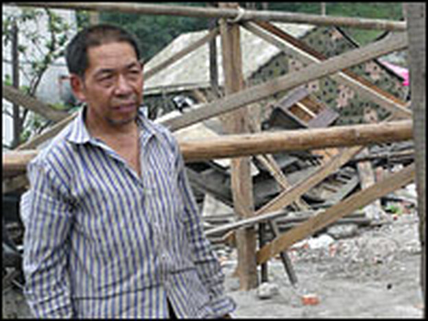 Wang Qifa stands beside the temporary shelter he is building for himself out of the remains of his devastated house.  He is even reusing the nails salvaged from the wreck of his last house.