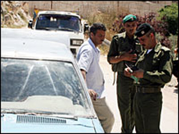 Mohammed Zakarni (left) is detained at a Palestinian security checkpoint in Jenin. Officers tell him his car will be confiscated because it's not registered and unfit to be on the road.