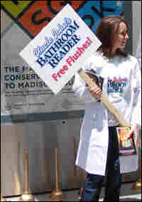 Lauren Fitting holds a sign promoting National Bathroom Reading Month