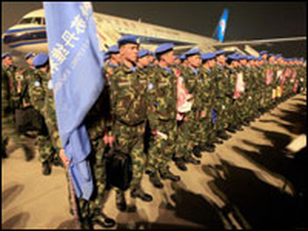 Chinese People's Liberation Army soldiers wear sky-blue United Nations berets, signifying membership in a Chinese peacekeeping unit destined for Darfur, as they prepare to leave Xinzheng International Airport in November.