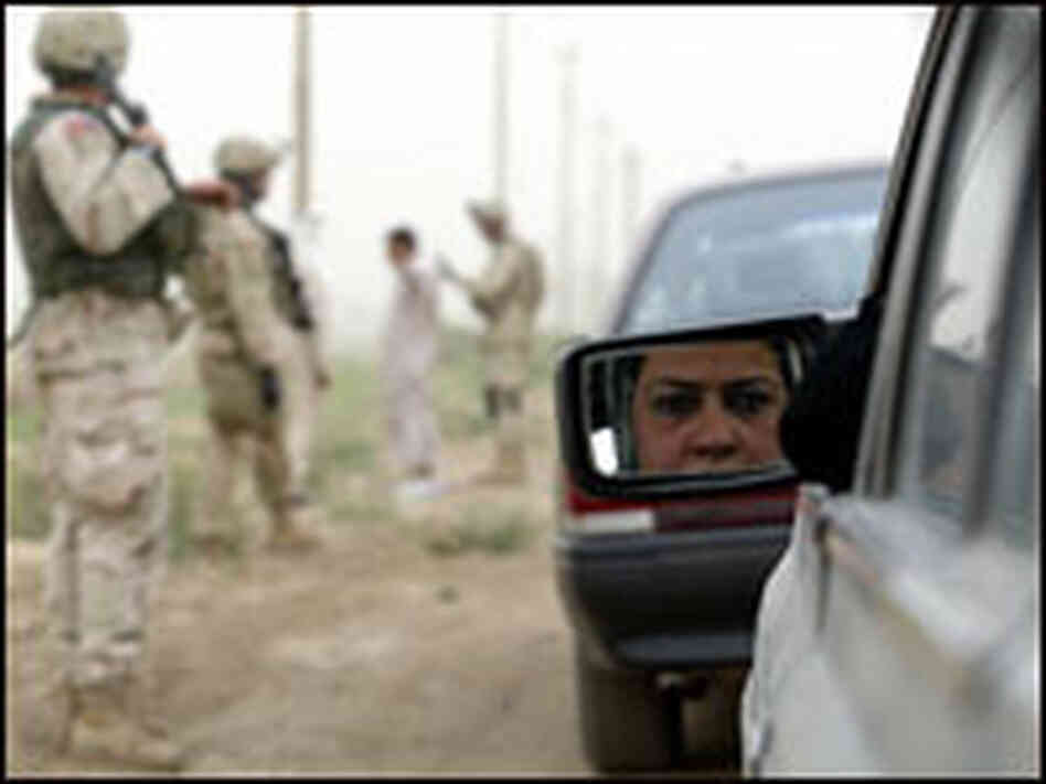 An Iraqi woman is reflected in the mirror of her car at a checkpoint south of Baghdad.