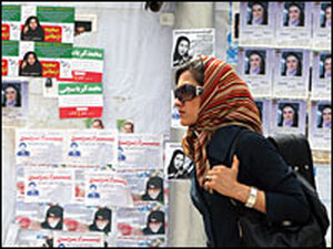An Iranian woman walks past election posters in northwest Tehran on Thursday.