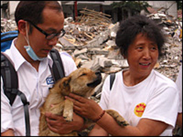Chen Yunlian (right), a retiree who runs a shelter for homeless dogs and cats, and a member of the Hong Kong SPCA hold Qianjin, one of the dogs who helped save a woman after the earthquake.