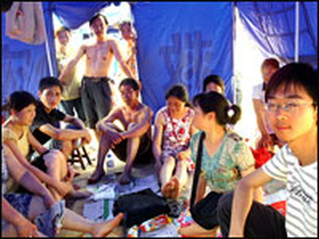 A 20-year-old English major at Mianyang University who goes by the name Frank shows NPR his family's blue tent in a tent city in Mianzhu. It was hot, humid and crowded.