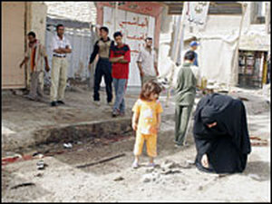 Iraqis inspect the site of a suicide bomb attack at