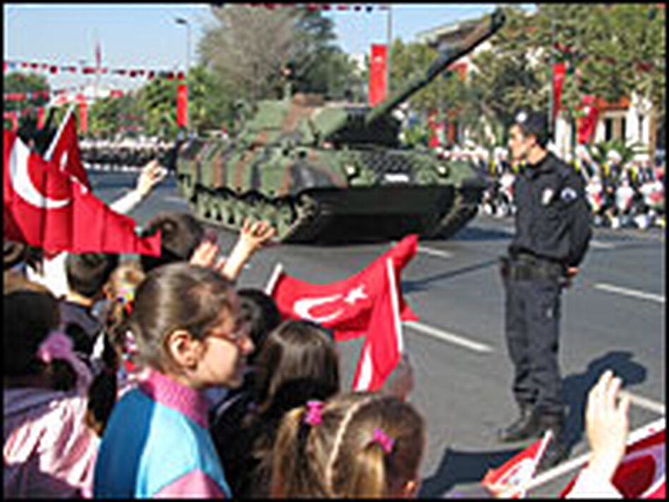 Flag-waving children cheer as a parade of soldiers and tanks moves past on Turkish Republic Day. Eighty-five years after a group of army officers founded the Turkish Republic, the military still plays a major role in politics.