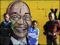 South African boys pose beside a wall mural portraying Jacob Zuma of the ANC