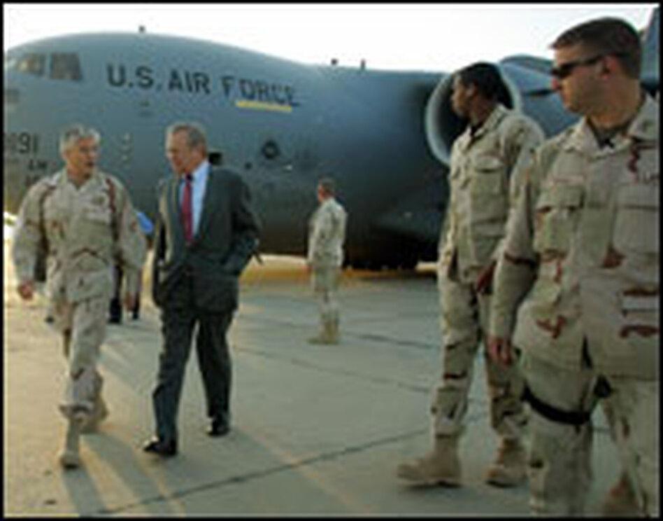 Defense Secretary Donald Rumsfeld (center) speaks with Gen. George Casey at Baghdad International Airport in April 2006.